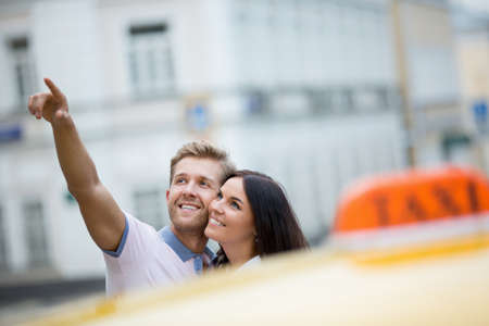 love life: Smiling young couple with taxi Stock Photo