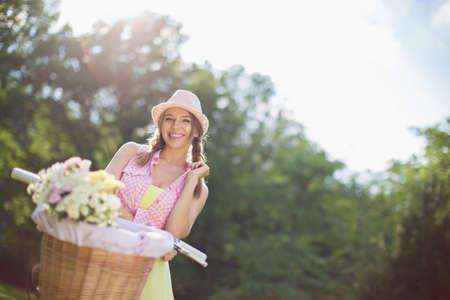 mujer alegre: Muchacha atractiva con una bicicleta en el parque
