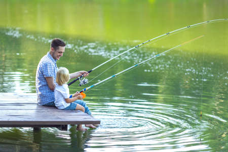 dad son: Dad and son fishing outdoors