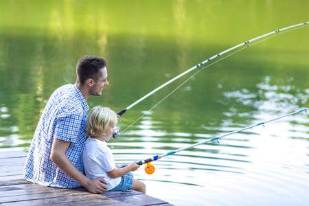 personas sentadas: Papá e hijo de pesca al aire libre Foto de archivo