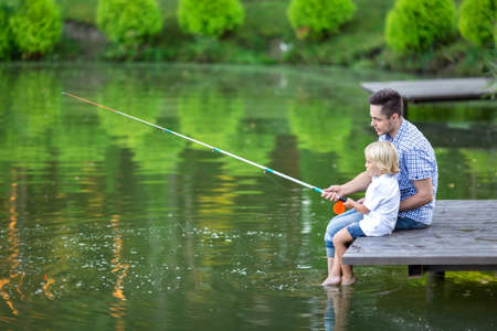 niños sentados: Padre e hijo de pesca en el lago