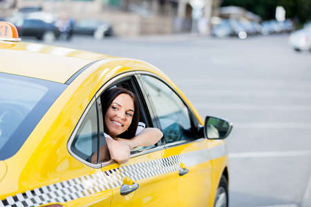 yellow taxi: Young woman in yellow taxi Stock Photo