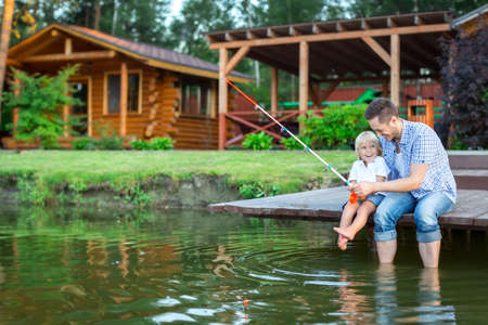 father with child: Father and son fishing outdoors