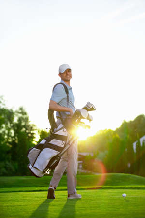 golf bag: Young man with a golf bag outdoors Stock Photo