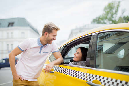 a yellow taxi: Young couple in a yellow taxi