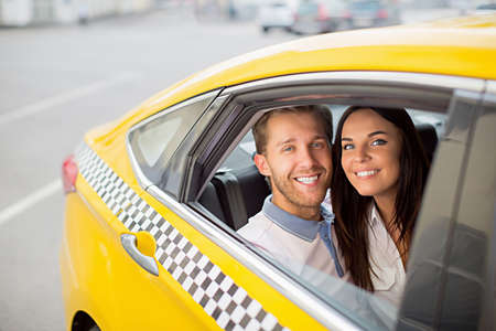 a yellow taxi: Attractive couple in a yellow taxi