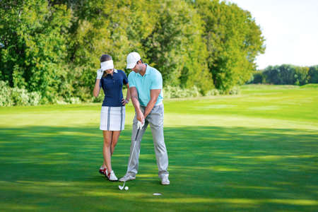 playing golf: Young couple playing golf