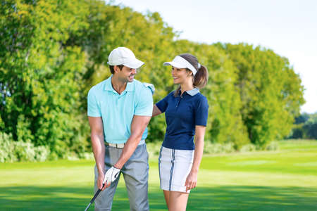playing golf: Smiling couple playing golf