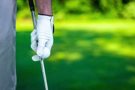golf glove: Mans hand with a ball and club