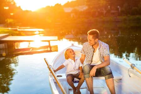 hijos: Padre e hijo en un barco en el lago