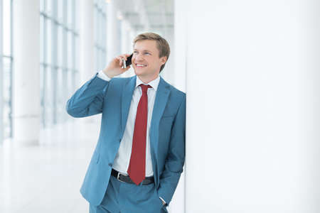 men talking: Businessman in suit with phone in office Stock Photo