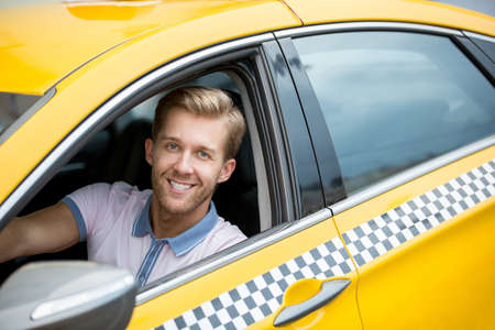 a yellow taxi: Smiling driver in a yellow taxi