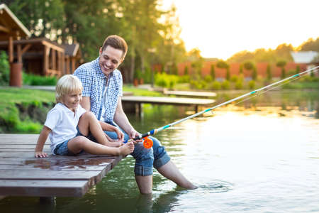 Dad and son fishing in summer