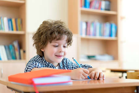 Little boy at a desk in classroom Stock Photo