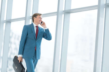 businessman phone: Businessman with phone in office