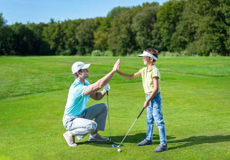 Father and son playing golf Standard-Bild