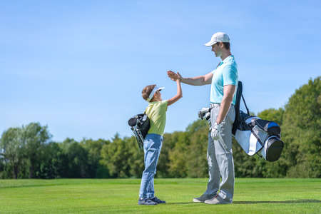 Father and son on golf course Stock Photo