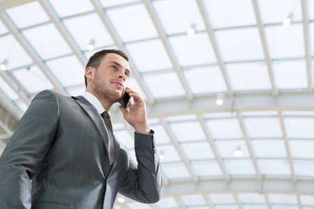 business man phone: Young businessman talking on phone