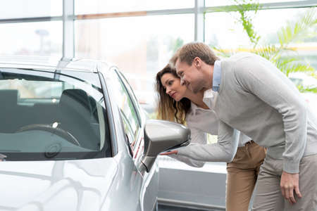 automobile dealership: Young couple with car in salon