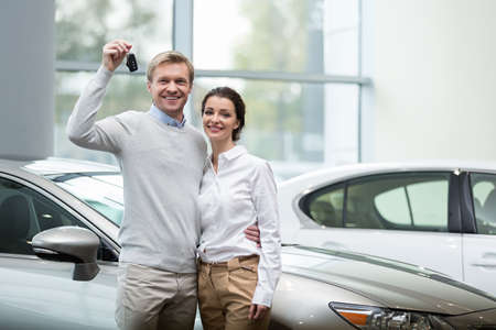 Couple buying a car in autocenter Foto de archivo