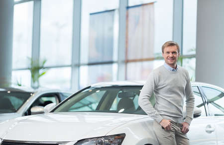 new car: Young man in car salon of cars