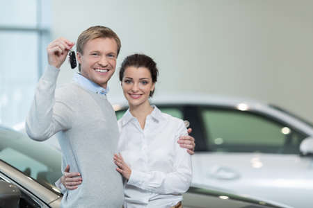 buying a car: Young couple with keys of car