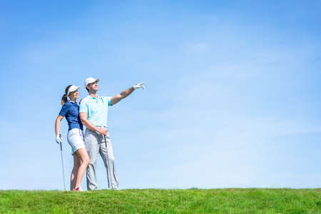 golf glove: Young couple playing golf outdoors