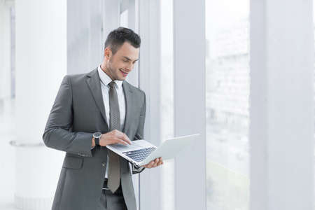 young businessman: Smiling businessman with laptop in office Stock Photo