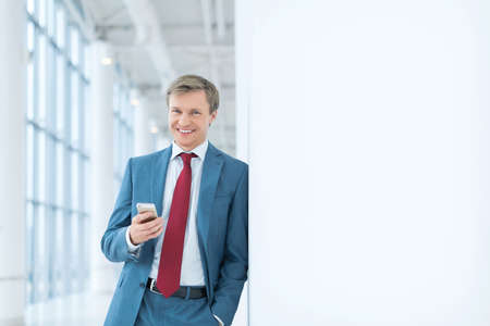 white suit: Young businessman with phone in office Stock Photo