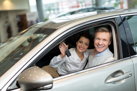 key: Attractive couple with keys in car Stock Photo