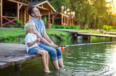 Dad with son fishing outdoors