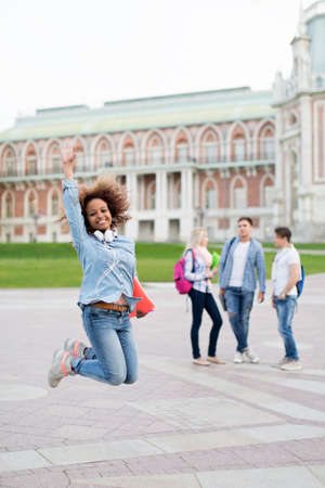 college campus: Jumping young girl outdoors Stock Photo