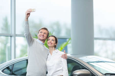 new car: Smiling couple making selfie indoors