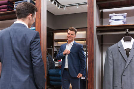 indoors: Young businessman at mirror indoors