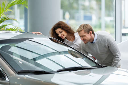 automobile dealership: Young couple buying cars
