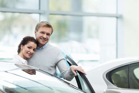 buying: Couple buying a car indoors