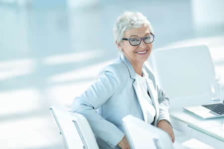 Caucasian woman: Elderly woman with laptop in office Stock Photo