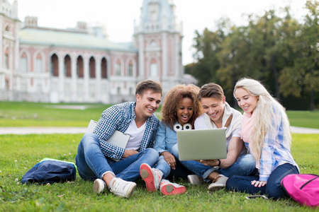 youth group: Young students with laptop outdoors Stock Photo