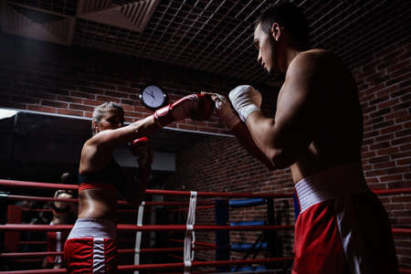 woman with boxing gloves: Fighting people in boxing ring