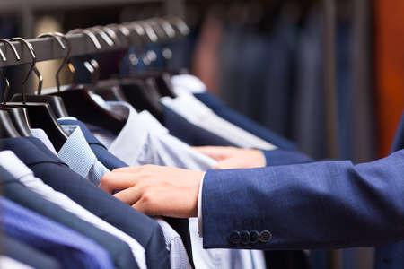 Männliche Hand, die ein Hemd wählt Standard-Bild