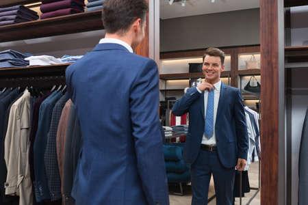 Young man in suit at a mirror Foto de archivo