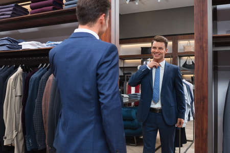 beautiful men: Young man in suit at a mirror Stock Photo