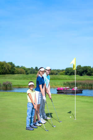 Smiling family in golf course photo