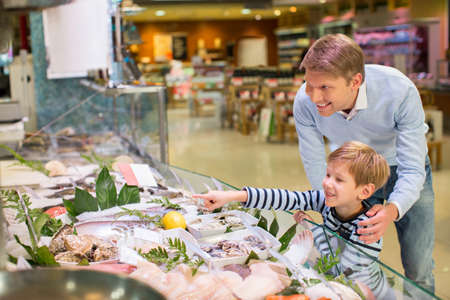 fish shop: Dad and son in a fish store