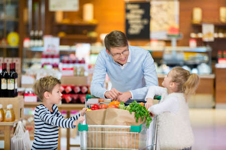 dad son: Dad and children with shopping cart Stock Photo