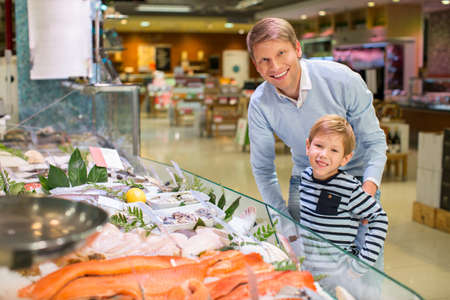 fish shop: Dad and son in a store