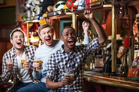 football party: Expression fans with beer indoors Stock Photo