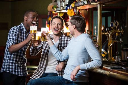 Uomo sorridente con una birra in casa