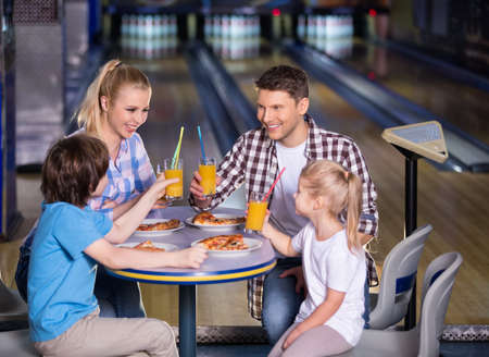 alley: Smiling family in bowling cafe