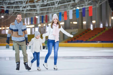 Family with child at ice-skating rink Foto de archivo